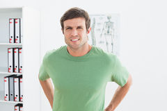 Portrait of a handsome young man with back pain Stock Photo