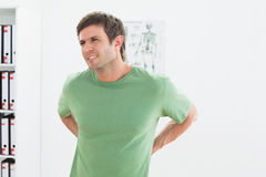 Portrait of a handsome young man with back pain. Standing in the medical office Stock Photography