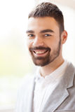 Portrait of Handsome Young Man. Handsome bearded man looking at camera with toothy smile while standing against blurred background, head and shoulders portrait Stock Images