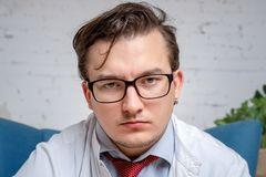 Portrait of a handsome young man in black glasses dressed as a psychotherapy doctor. Looking into the camera, seriously listening stock photos