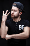 Portrait of handsome young man in black shirt and cap on black background. rapper. Portrait of a handsome young brunette man in a black shirt and cap on a black Stock Photos