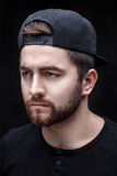 Portrait of handsome young man in black shirt and cap on black background. rapper. Portrait of a handsome young brunette man in a black shirt and cap on a black Royalty Free Stock Photo