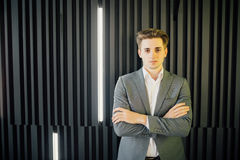 Portrait of a handsome young man in a business suit with crossed hands against wooden dark wall in modern office. Portrait of a handsome young man in a business Royalty Free Stock Image