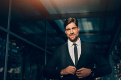 Portrait of handsome young man in business suit. Looking at camera. He is standing in a modern building Royalty Free Stock Photo
