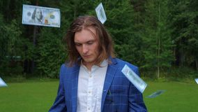 Portrait of a handsome young man in a business suit in a park around whom money is flying. Portrait of a long-haired handsome young man in a business suit in a stock video footage