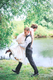 Portrait of a handsome young man carrying attractive woman on his back outdoors . Fun couple. Bride and gr stock images