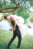 Portrait of a handsome young man carrying attractive woman on his back outdoors . Fun couple. Bride and gr royalty free stock photography