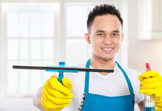 Man cleaning the house. Portrait of handsome young man cleaning the house stock photography