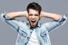 Handsome young man covering her ears over gray background. Royalty Free Stock Photography
