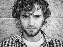Portrait of handsome young man with curly hair and beard Royalty Free Stock Images