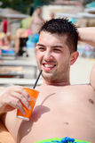 Portrait of handsome young man drinking juice on the pool Stock Image