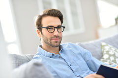 Portrait of handsome young man with eyeglasses reading book Royalty Free Stock Images