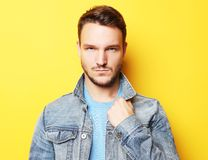 Portrait of a handsome young man, fashion model. Posing over yellow wall. Royalty Free Stock Photography