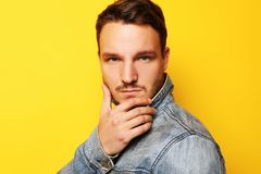 Portrait of a handsome young man, fashion model. Posing over yellow wall. Lifestyle and fashion concept. Stock Image