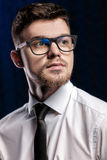 Portrait of handsome young man with glasses and white shirt on dark background Royalty Free Stock Photos