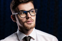 Portrait of handsome young man with glasses and white shirt on dark background Royalty Free Stock Images