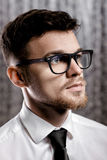 Portrait of handsome young man with glasses and white shirt on grey background Royalty Free Stock Photography