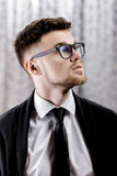 Portrait of handsome young man with glasses and white shirt on grey background Stock Photo