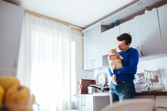 Portrait of handsome young man holding cat on the kitchen stock images
