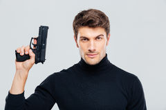 Portrait of handsome young man holding a gun Royalty Free Stock Photos