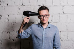 Portrait of handsome young man in jeans clothes and eyeglasses with hairdryer looking to camera smiling, standing Stock Image