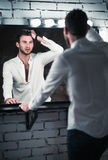 Portrait of handsome young man in jeans and shirt looking into mirror Royalty Free Stock Photos