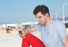 Portrait of a handsome young man listening on mp3 player outdoors Stock Photo