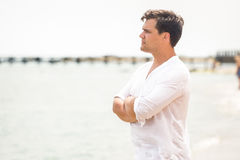 Portrait of handsome young man looking on the horizon at ocean Stock Photos