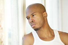 Portrait of a handsome young man looking out of window Stock Photo