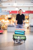 Handsome Young Man With Luggage In Cart At Airport Royalty Free Stock Images