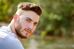 Portrait of handsome young man outdoors in nature. Looking in camera royalty free stock photography