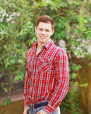 Portrait of handsome young man in plaid shirt outdoors. Summer day royalty free stock images