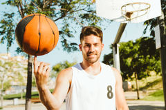 Portrait of handsome young man playing basketball on court. Royalty Free Stock Photos