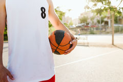 Portrait of handsome young man playing basketball on court. Stock Image