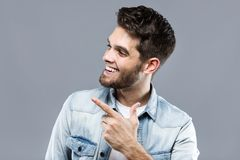 Handsome young man posing and looking sideways over gray background. Portrait of handsome young man posing and looking sideways over gray background Stock Photo