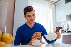 Portrait of handsome young man pours tea with cat on the kitchen. Portrait of handsome young man playing with cat in the kitchen stock images