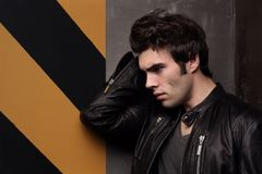 Portrait of a handsome young man in profile. Stylish in appearance. A black leather jacket. Posing on wall background royalty free stock photography