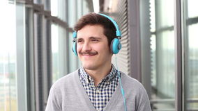 Portrait of handsome young man puts on headphones and listens to music stock footage