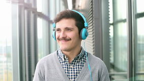 Portrait of handsome young man puts on headphones and listens to music stock video