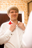 Portrait of handsome young man putting on red bow tie Royalty Free Stock Image