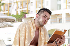 Portrait of handsome young man reading a book on the pool Stock Photos
