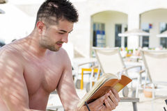 Portrait of handsome young man reading a book on the pool Royalty Free Stock Images