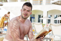 Portrait of handsome young man reading a book on the pool Stock Image