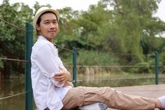 Portrait of handsome young man relaxing sit on bridge floor at the park outdoors Stock Photo