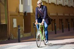 Handsome young man riding a bike in the street. Portrait of handsome young man riding a bike in the street Royalty Free Stock Photo