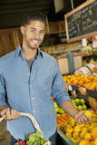 Portrait of handsome young man shopping for fruits in market Royalty Free Stock Photography