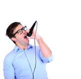 Portrait of handsome young man singing on microphone isolated o Royalty Free Stock Photos