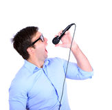 Portrait of handsome young man singing on microphone isolated o Stock Photography