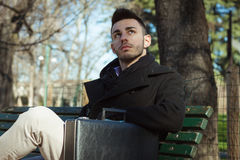 Portrait of a handsome young man sitting on a bench Royalty Free Stock Photos