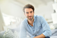 Portrait of handsome young man sitting on sofa Stock Images